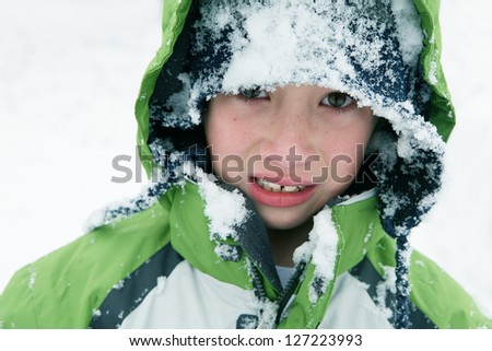 Young Boy with an Unhappy Expression from Falling in Snow - stock photo