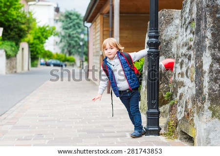 Young boy with backpack ready to go back to school - stock photo