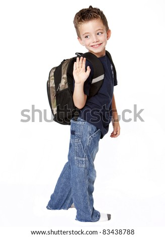 Young boy with backpack waving goodbye - stock photo