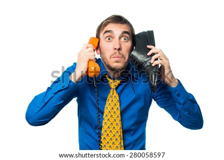young boy with blue shirt and yellow tie on the phone with a shoe and orange phone , isolated on white background - stock photo