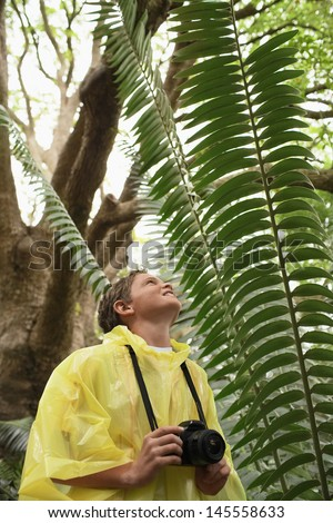 Young boy with camera looking at large fern in forest - stock photo