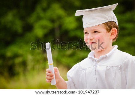 Young boy with cap and gown and certificate for preschool graduation - stock photo
