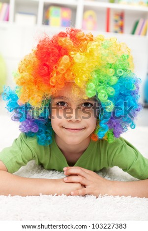 Young boy with clown wig laying on the floor smiling - stock photo