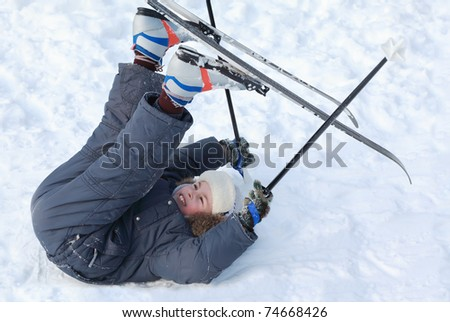 Young boy with cross-country skis and poles lying on snow and put up feet on pure white snow - stock photo