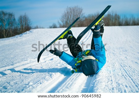 Young boy with cross-country skis lying on snow - stock photo
