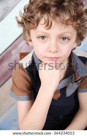 Young boy with curly blonde hair and blue shirt - stock photo
