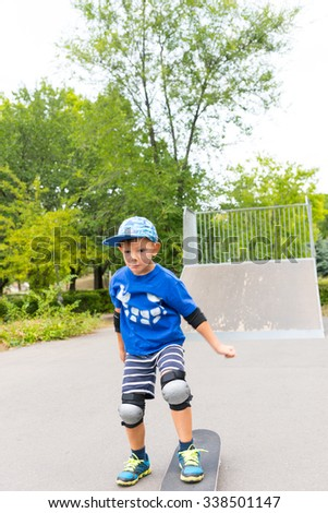 Young Boy with Determined Expression Standing in Skate Park with One Foot on Skateboard in front of Ramp on Summer Day - stock photo