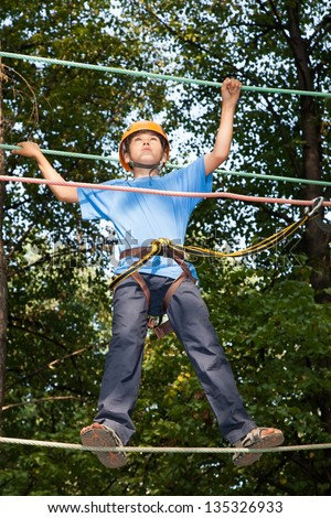 Young boy with equipment climber moves on ropes. The boy looks up. - stock photo