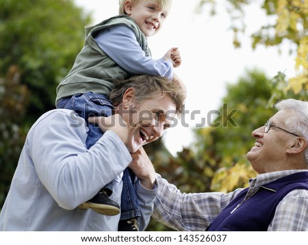 Young boy with father and grandfather enjoying together in park - stock photo