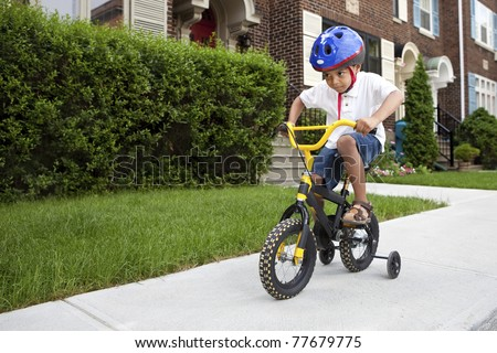 Young boy with helmet riding his first bicycle with training wheels - stock photo