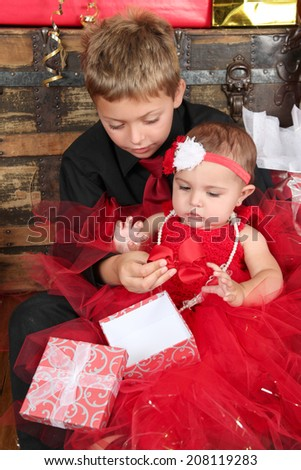 Young boy with his baby sister opening a gift box - stock photo