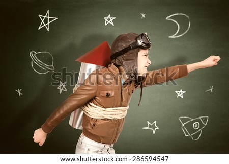 Young boy with home made rocket ready for adventure in classroom - stock photo
