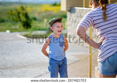 Young Boy with Ice Cream Moustache Standing with Hands Behind Back and Laughing in front of Angry Mother Standing with Hands on Hips Outdoors - stock photo