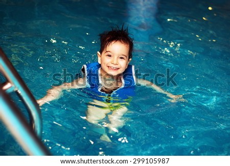 Young boy with inflatable swimming vest in the pool, has a happy smile.  Eye contact. - stock photo