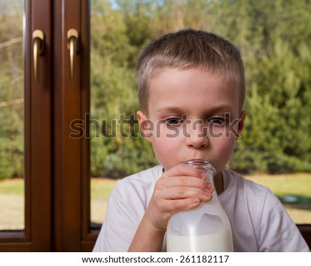 Young boy with milk bottle.  Focus on hand. - stock photo