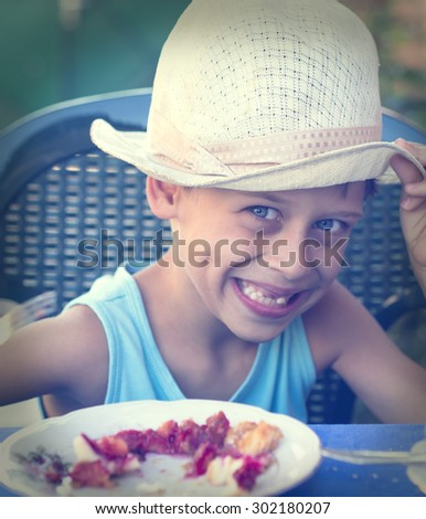 young boy with old hat eating  - stock photo