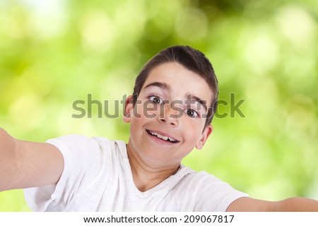 Young boy with phone becoming a self-portrait - stock photo