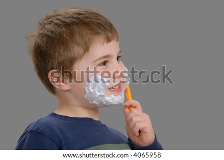 Young boy,with shaving cream on face, removing it with razor, isolated - stock photo