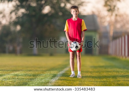 Young boy with soccer ball posing for picture - stock photo