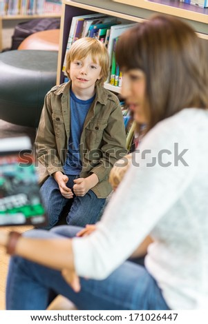 Young boy with teacher in school library - stock photo
