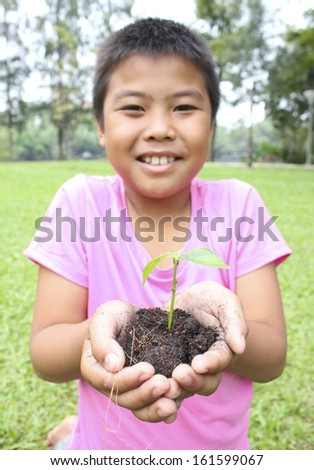Young boy with two hands holding sapling soil. - stock photo