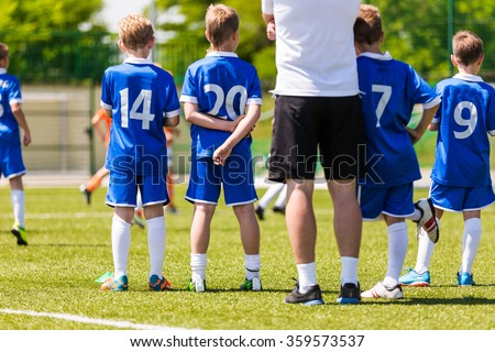 Young boys and soccer coach watching football match. Youth reserve players ready to play - stock photo