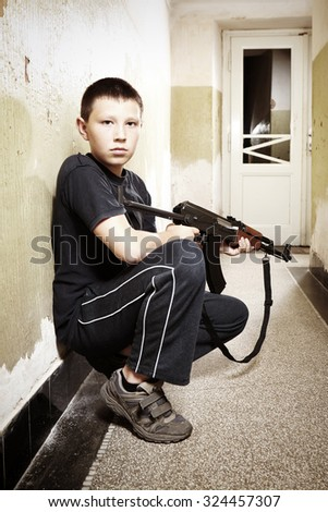Young boys handling dangerous automatic gun - stock photo