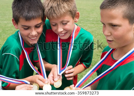 young boys holding  gold medals - stock photo