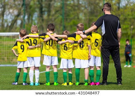 Young boys in soccer team standing united together on the sports field. Penalty soccer game during soccer football tournament for youth european teams. - stock photo