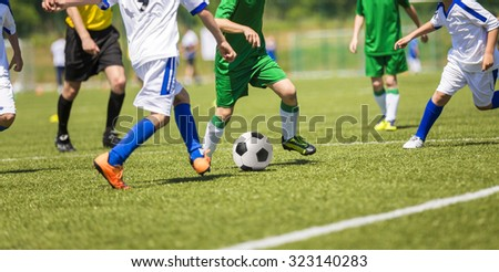 Young boys play football soccer match. Running players of two teams. White and green uniforms. - stock photo