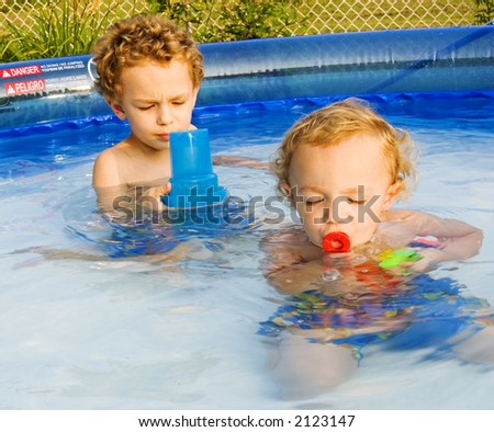 Young boys playing in swimming pool in back yard - stock photo