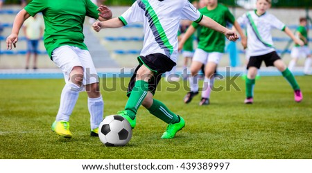 Young Boys Playing Soccer Game on the Professional Football Pitch. Football Soccer Tournament for Youth Teams. - stock photo