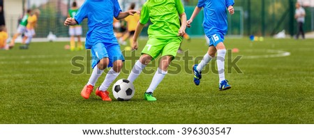 Young boys playing youth soccer football game. Sport tournament for kids - stock photo