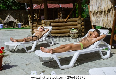 young boys taking a break from swimming and resting on a chaise lounge - stock photo