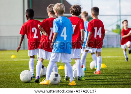 Young Boys Training Soccer Football on the Green Pitch of the Football Stadium.  Training session for youth boys team before the tournament soccer match. Young boys kicking soccer ball. - stock photo