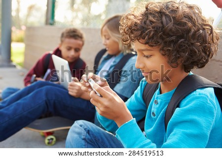 Young Boys Using Digital Tablets And Mobile Phones In Park - stock photo