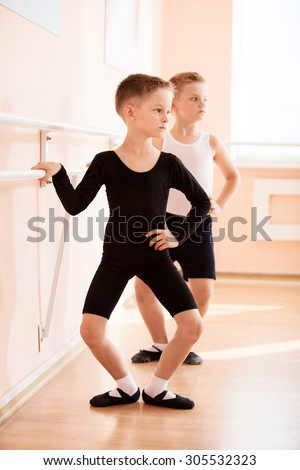 Young boys working at the barre in a ballet dance class. - stock photo