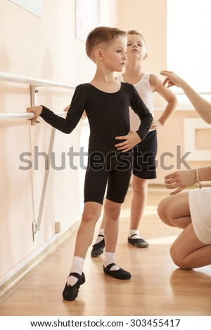 Young boys working at the barre in a ballet dance class. Teacher adjusting the position of one of them. - stock photo