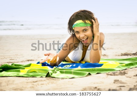 young Brazil supporter on beach in team colors with flag - stock photo