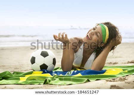 young Brazil supporter on beach in team colors with football - stock photo