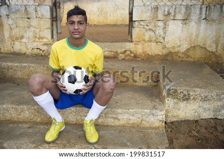 Young Brazilian football player holding soccer ball sitting outdoors in his favela neighborhood - stock photo