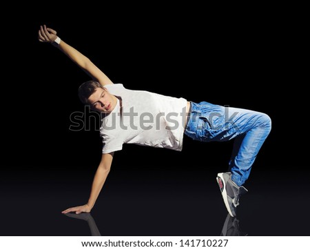 Young break dancer standing on one hand and legs - stock photo