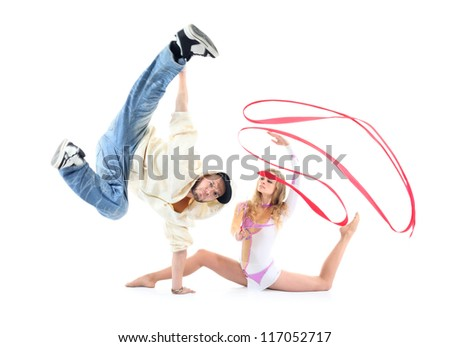 Young breakdancer stands on one hand and leg held up and graceful gymnast with red ribbon sits on floor isolated on white background. - stock photo