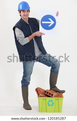 young bricklayer in studio holding sign with arrow - stock photo