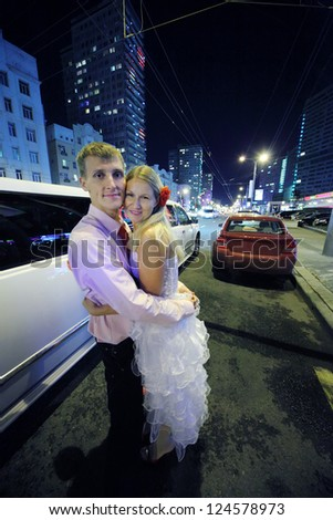 Young bride and groom embrace and stand near white limousine at night. Pink wedding. - stock photo