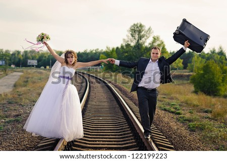 young bride and groom on a railway track - stock photo