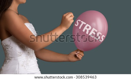 Young bride in wedding dress lets a Balloon burst with a needle - stock photo