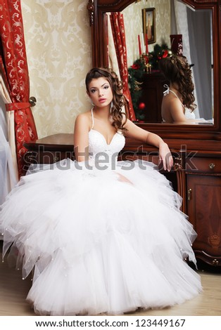 young bride looks at herself in the mirror - stock photo