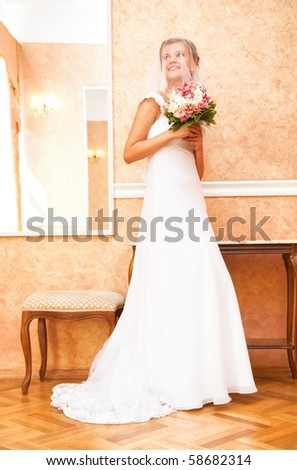 Young bride with flowers indoors. - stock photo