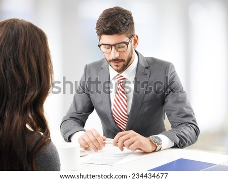Young broker consulting with client while sitting at office.  - stock photo
